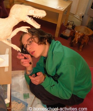 Catherine adding paper mache clay to Velociraptor model